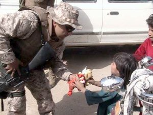 Soldier in Afghanistan offers a Beanie  Baby to an Afghani child. This Beanie Baby was donated by AnySoldier supporters. Photo used courtesy AnySoldier.com